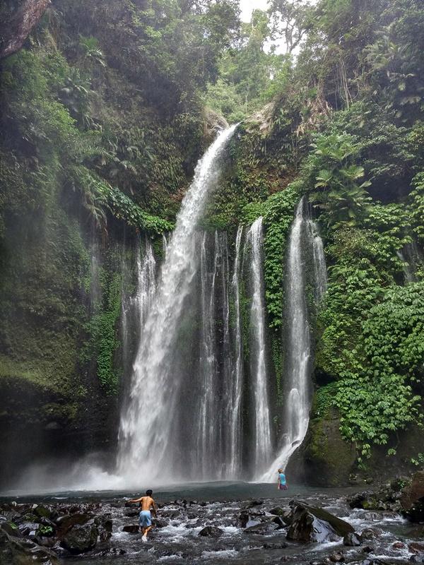Personas bañándose en la cascada de Tiu Kelep